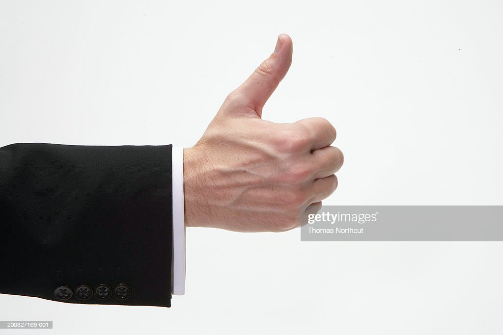 Man giving thumbs up sign, close-up of hand, side view : Stock Photo