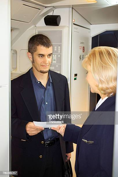 Man giving ticket to flight attendant