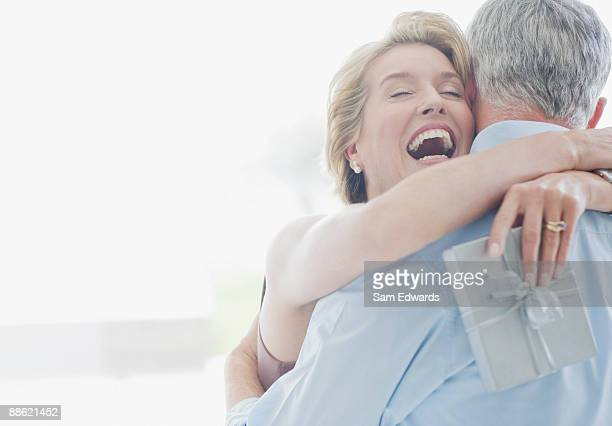 man giving wife anniversary gift - anniversary stock pictures, royalty-free photos & images