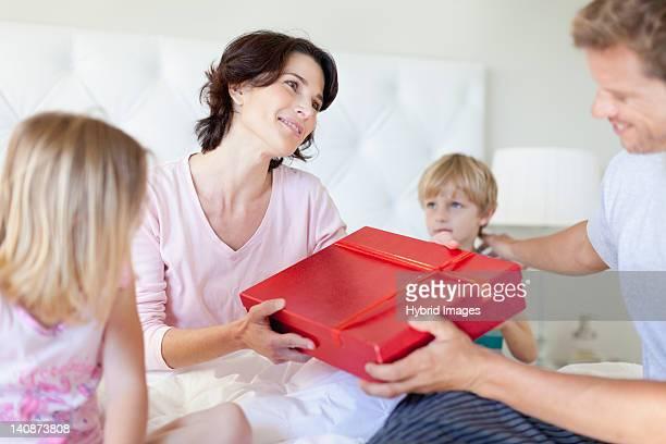 Hombre dando mujer presente en la cama