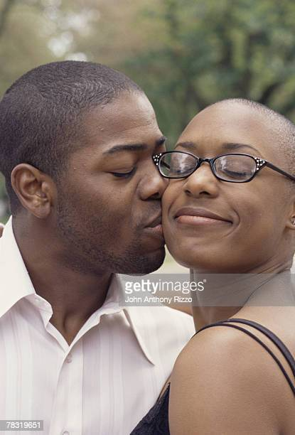 Man giving woman a kiss on cheek