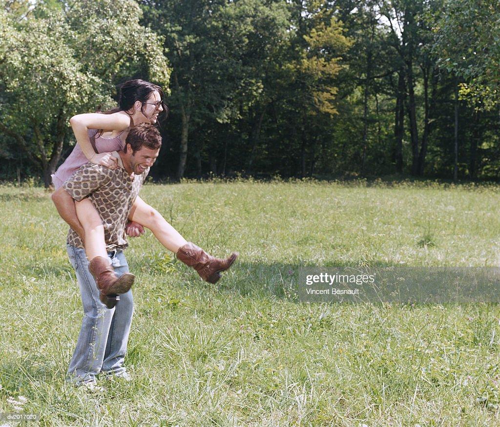 Man Giving Woman a Piggyback : Stock Photo