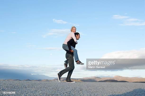 mulher homem dando um piggy-back ride - cavalitas imagens e fotografias de stock