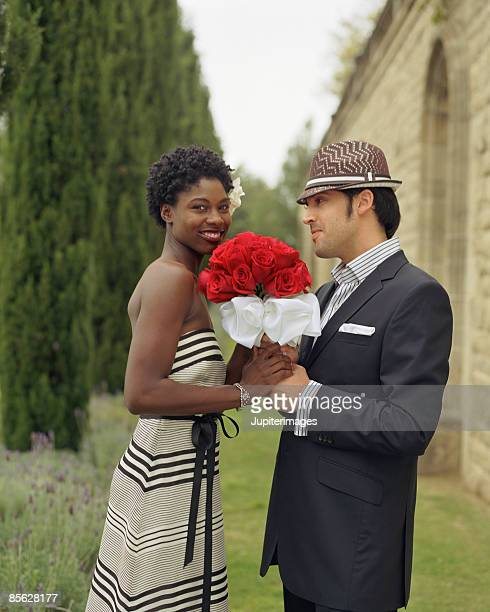 Man giving woman bouquet of roses