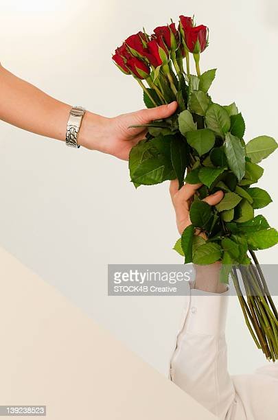 Man giving woman bunch of red roses