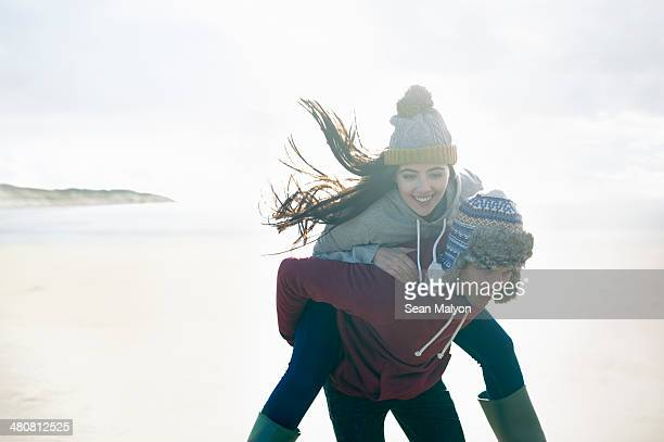 man giving woman piggy back, brean sands, somerset, england - sean malyon stock pictures, royalty-free photos & images