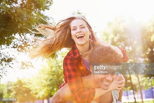 man giving woman piggy back having fun