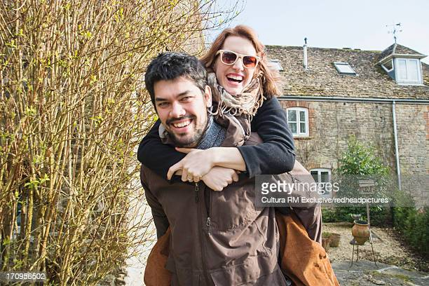 Man giving woman piggy back