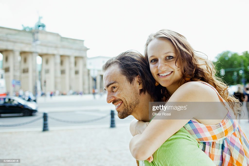 Man giving woman piggy back ride in city : Stock-Foto