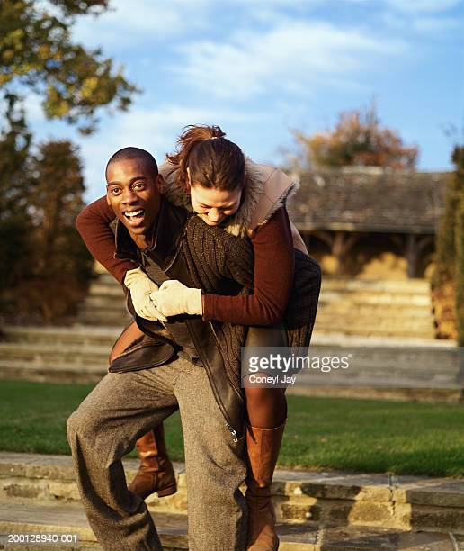 Man giving woman piggyback outdoors