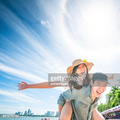 Man giving woman piggyback ride at the beach.
