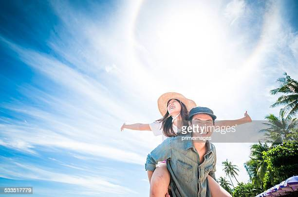 Man giving woman piggyback ride at the beach.