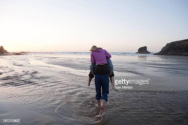Hombre dando mujer caballito paseo en la playa