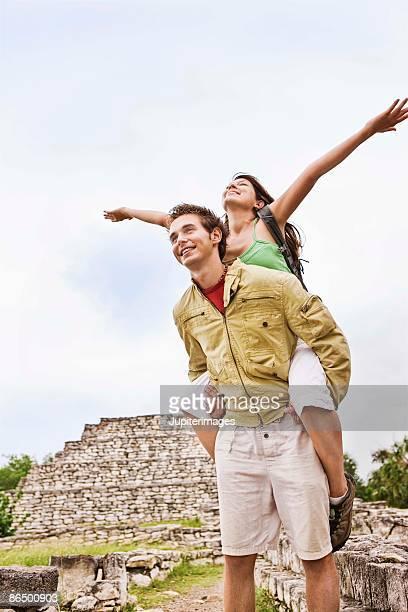 Man giving woman piggyback ride outdoors