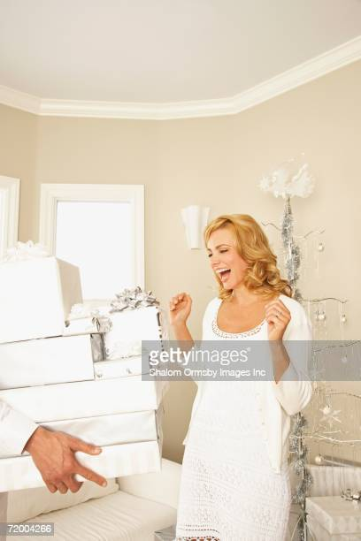 Man giving woman stack of gifts on Christmas
