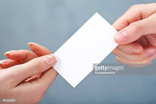 Man giving women blank business card on gray background