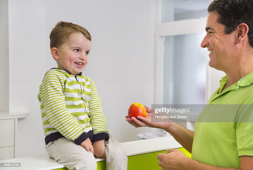 Man giving young boy apple : Stock Photo
