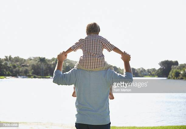man giving young boy shoulder ride outdoors at park by a lake - carrying a person on shoulders stock photos and pictures