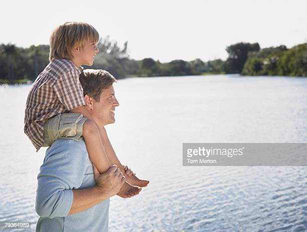 Man giving young boy shoulder ride outdoors at park by a lake