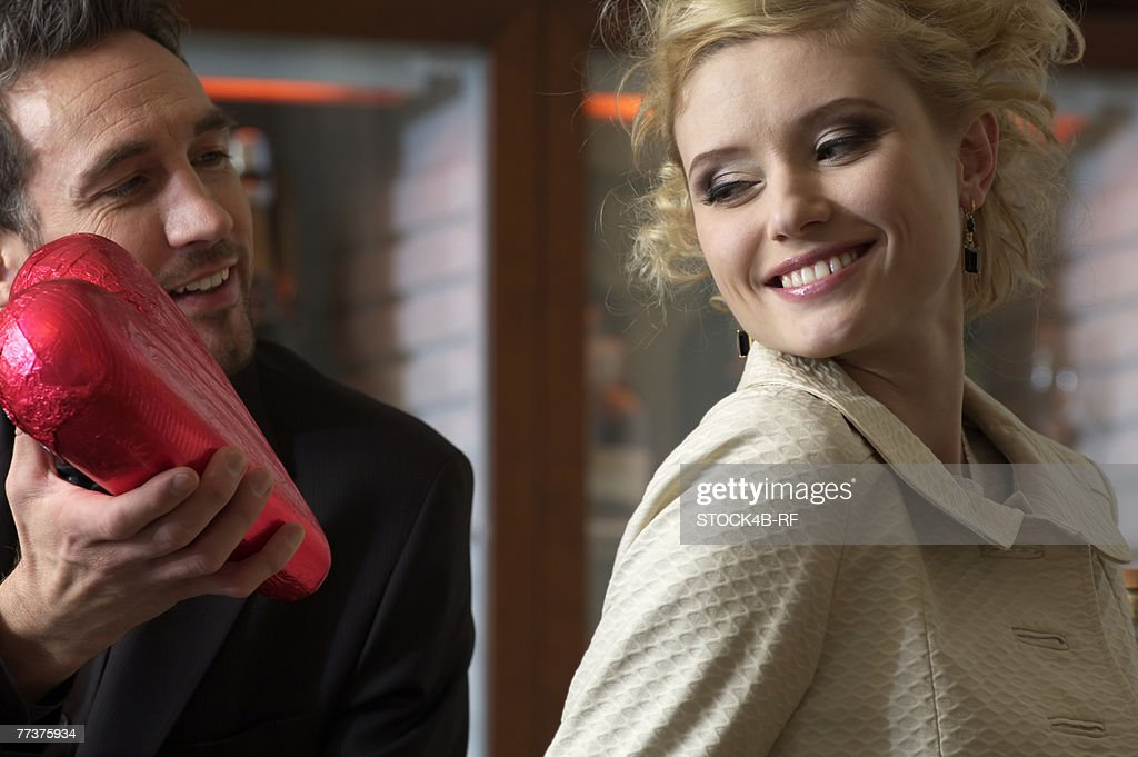 Man giving young woman a chocolate heart : Photo