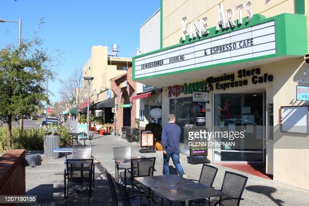A man glances into ZombieRunner coffee shop as he strides along a quiet sidewalk in downtown Palo Alto a social hub for tech workers and students at...