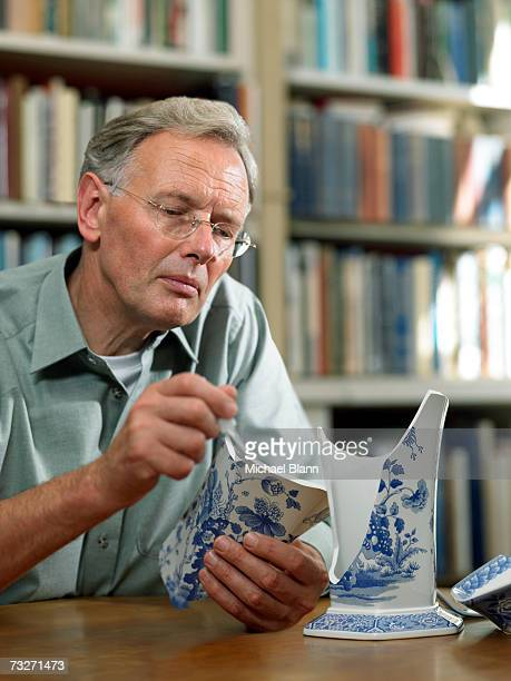 Mann gluing eine vase auf der Rückseite zusammen
