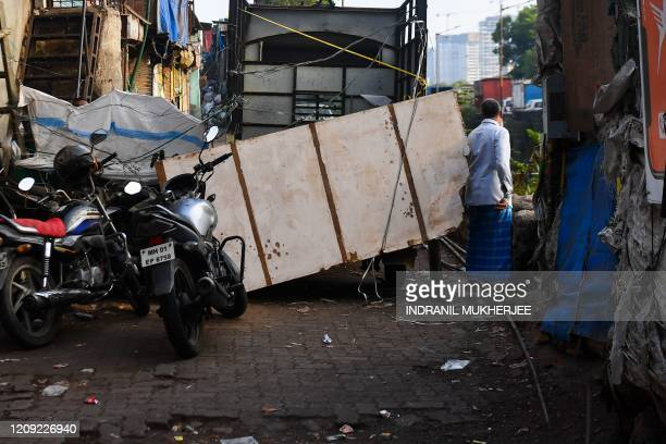 A man goes past a barricade put up by residents inside the Dharavi slum during a governmentimposed nationwide lockdown as a preventive measure...