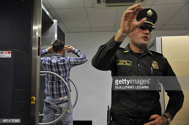 A man goes through a body scanner next to a policeman at El Dorado international airport in Bogota Colombia on September 25 2015 Trafficking drugs...