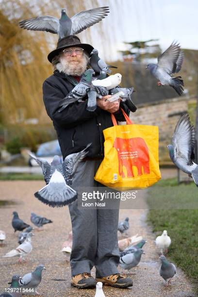 Man goes through his daily routine of feeding the birds near the Great Ouse river on January 19, 2021 in Godmanchester, United Kingdom.