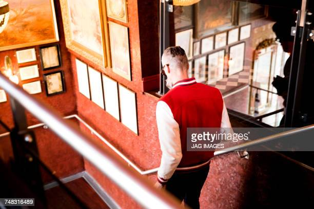 Man going down stairs in bar and restaurant, Bournemouth, England