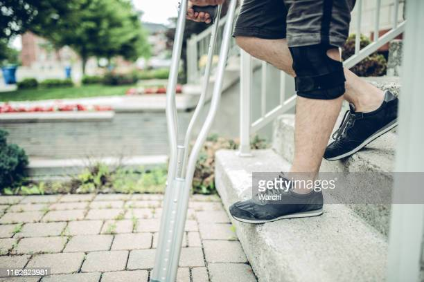 man going down the stairs with crutches - down on one knee stock pictures, royalty-free photos & images