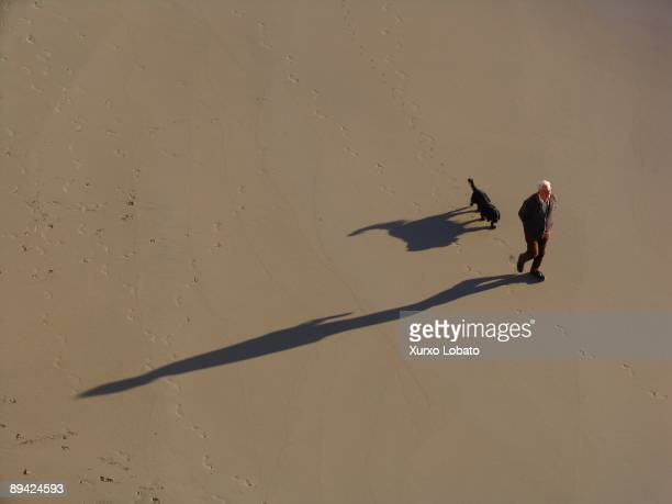 Man going for a walk with their dog at the Orzan Beach La Coruna