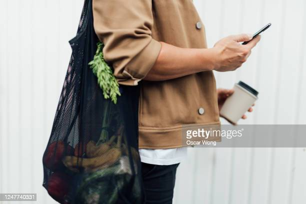 man going grocery shopping with a reusable shopping bag - cultures stock pictures, royalty-free photos & images