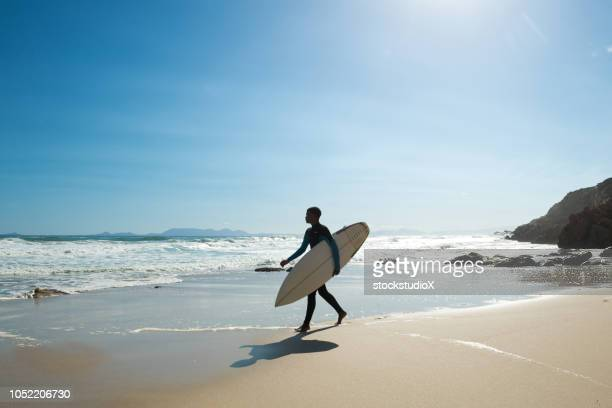 man going surfing along a stunning coastline - south africa stock pictures, royalty-free photos & images