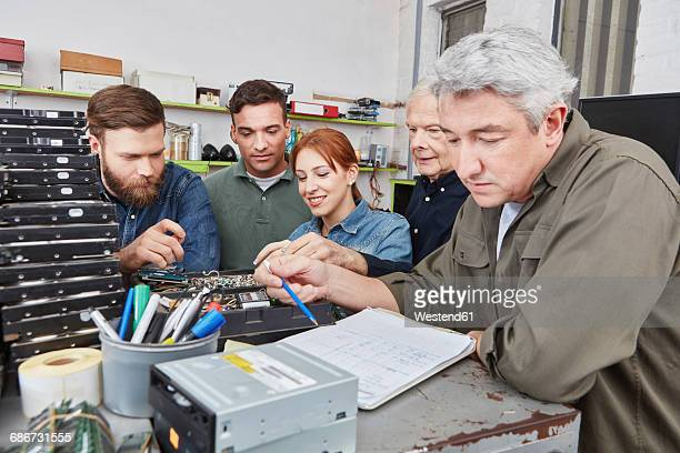 Man going through check list in computer recycling plant