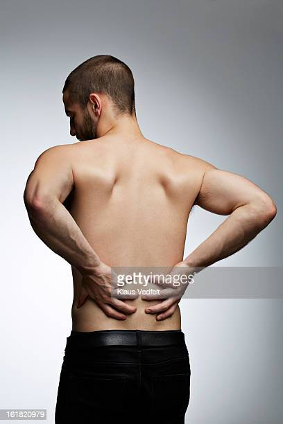 man grabbing lower back because of pain - lower back - fotografias e filmes do acervo