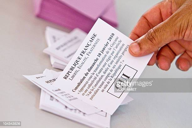 A man grabs a ballot in the polling station of Cayenne on the French South American territory of Guiana on January 10 for the referendum on the...