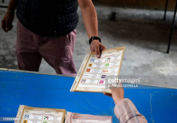 Man grabs an electoral ballot at a polling station during midterm elections in Mexico City, on June 6, 2021. - Mexicans began voting Sunday in...
