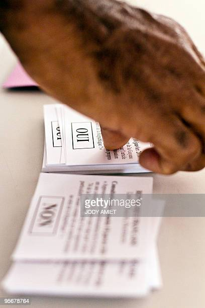 A man grabs ballots in the polling station of Cayenne on the French South American territory of Guiana on January 10 for the referendum on the status...