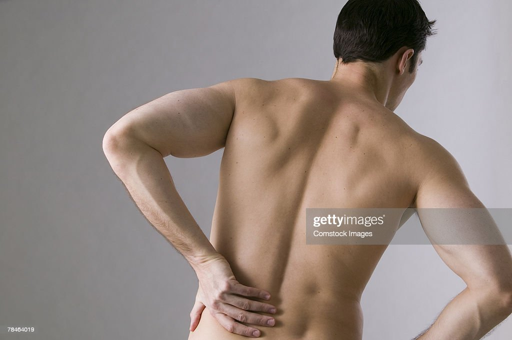 Man grasping his back in pain : Stock Photo