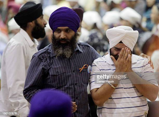 A man grieves as community members pay respects to the six victims in the mass shooting at the Sikh Temple of Wisconsin at the Oak Creek High School...