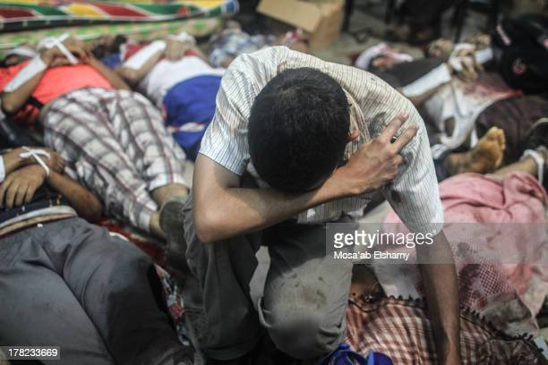 CONTENT] A man grieves as he looks at one of many bodies laid out in a make shift morgue after Egyptian security forces stormed two huge protest...