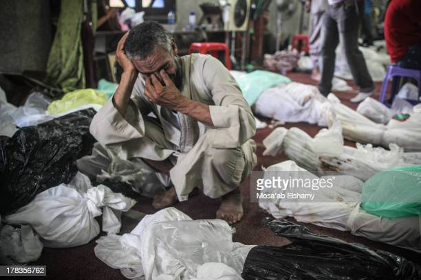 Man grieves as he looks at one of many bodies laid out in a make shift morgue after Egyptian security forces stormed two huge protest camps at the...