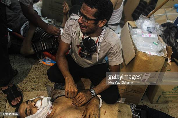 Man grieves as he looks at one of many bodies laid out in a makeshift morgue after Egyptian security forces stormed two huge protest camps at the...