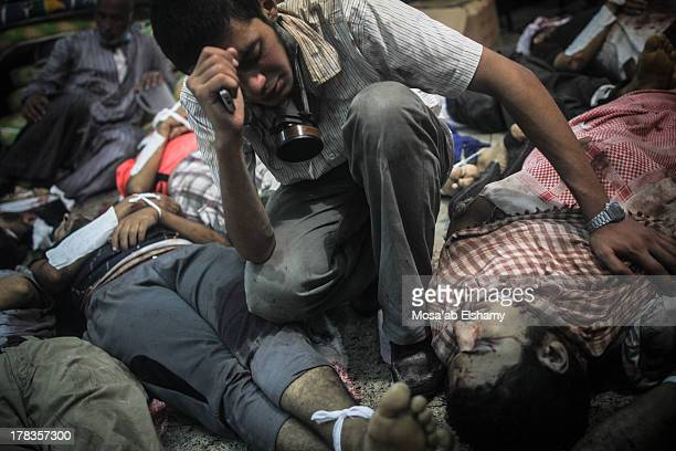CONTENT] A man grieves as he looks at one of many bodies laid out in a makeshift morgue after Egyptian security forces stormed two huge protest camps...