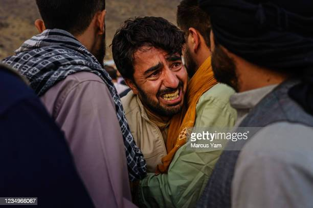Man grieves during a mass funeral for members of a family was killed in a U.S. Drone airstrike, in Kabul, Afghanistan, Monday, Aug. 30, 2021.