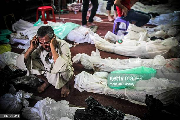 Man grieves next to dead bodies laid at Iman mosque which was turned into a makeshift morgue following the violent dispersal of Rabaa Adaweya square...