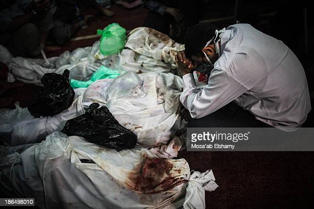 CONTENT] A man grieves next to dead bodies laid at Iman mosque which was turned into a makeshift morgue following the violent dispersal of Rabaa...