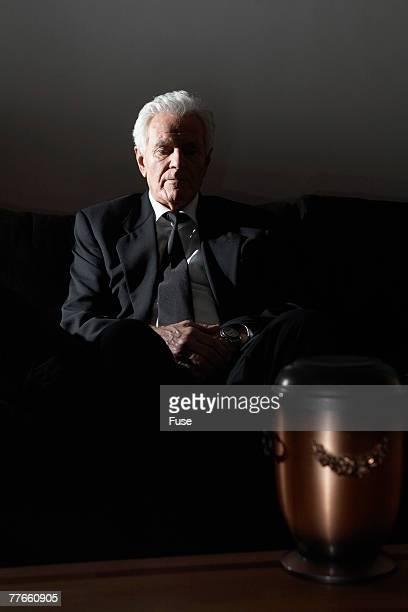 Man Grieving near Funeral Urn