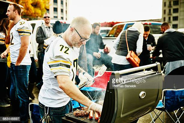 Man grilling at barbecue during tailgating party